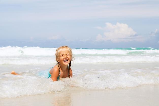 Klein meisje baadt in de zee op het strand met wit zand