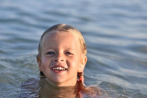Klein meisje baadt in de zee, portret, nat haar