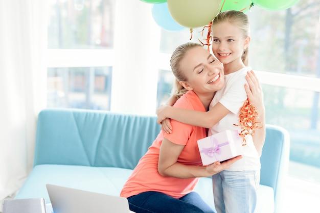 Klein meisje bereid geschenk voor moeder. ze houdt ballonnen vast.
