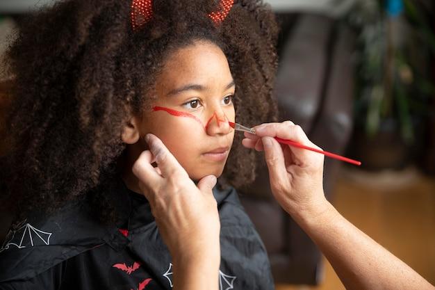 Klein meisje bereidt zich voor op halloween met een duivelskostuum