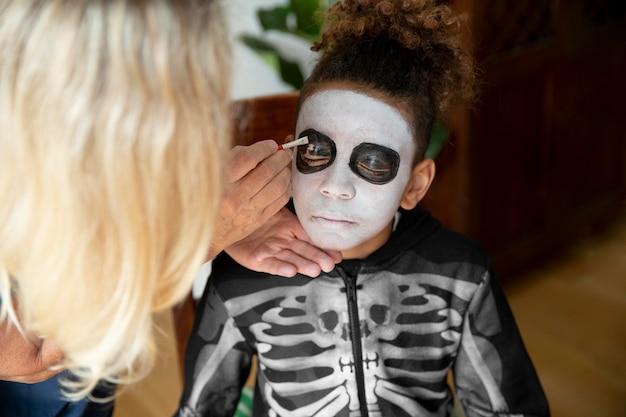 Klein meisje bereidt zich voor op halloween met een skeletkostuum Gratis Foto