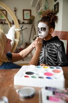 Klein meisje bereidt zich voor op halloween met een skeletkostuum