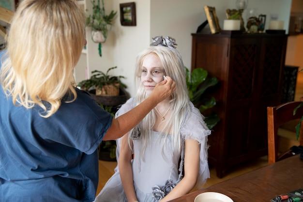 Klein meisje bereidt zich voor op halloween met een spookkostuum