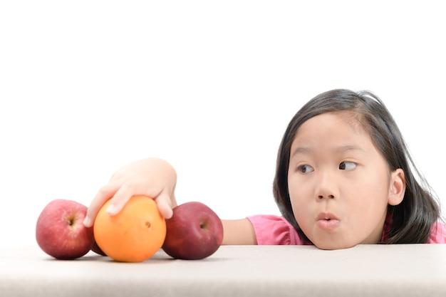 Klein meisje bereikt oranje op geïsoleerde tabel
