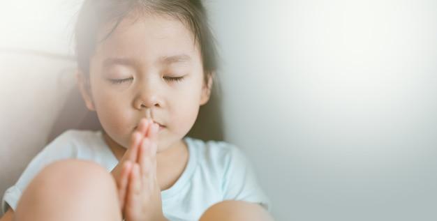 Klein meisje bidden. handen gevouwen in gebed concept voor geloof, spiritualiteit en religie.
