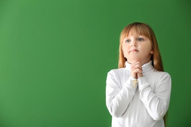 Klein meisje bidden op kleuroppervlak