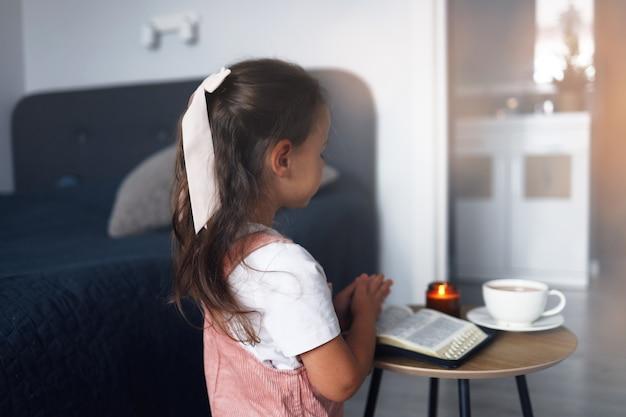 Klein meisje bidt in de ochtend. klein meisje bidden met de hand, handen gevouwen in gebed geloof, spiritualiteit en religie concept.