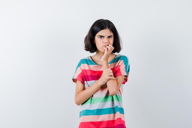 Klein meisje bijt vingers terwijl ze de hand op de onderarm houdt in een t-shirt, spijkerbroek en er opgewonden uitziet, vooraanzicht.