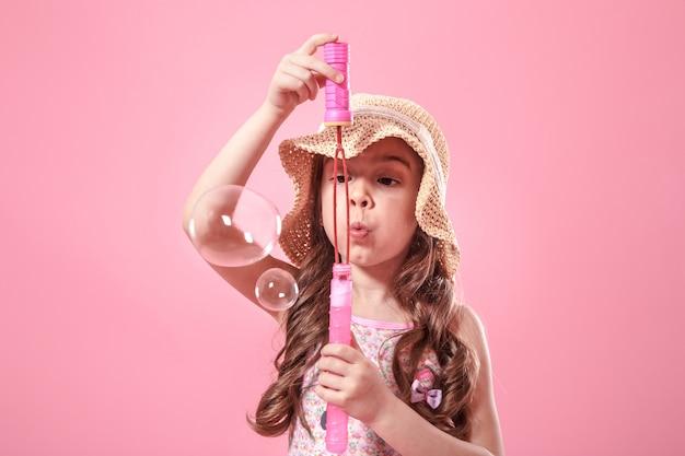 Klein meisje blaast zeepbellen op gekleurde achtergrond