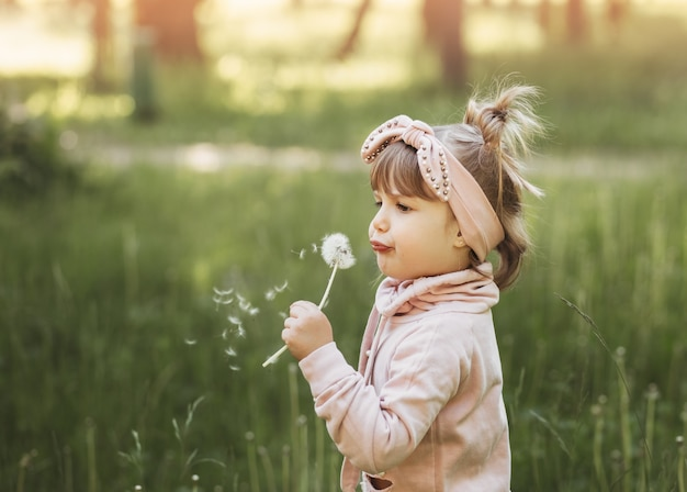 Klein meisje blazen op witte paardebloem in zomer park