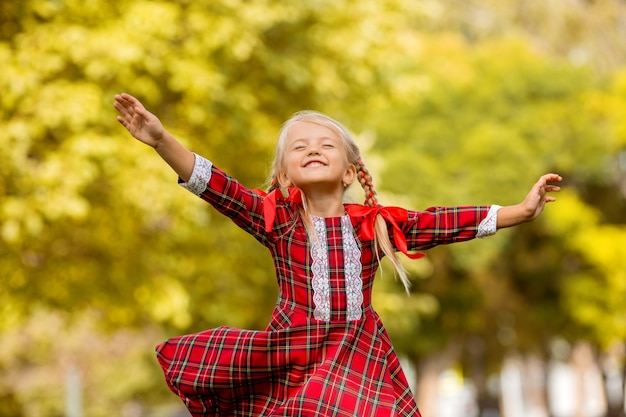 Klein meisje blonde eerste grader rode plaid jurk lachend in de straat
