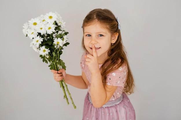 Klein meisje boeket van lentebloemen houden en om stilte vragen
