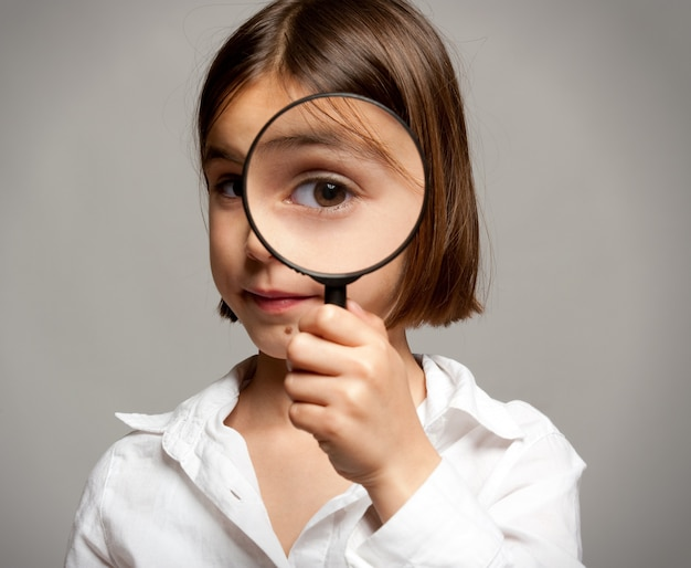 Klein meisje camera kijken door vergrootglas