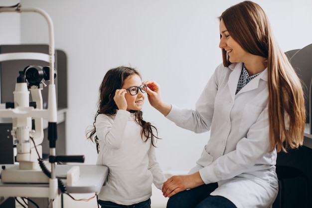 Klein meisje controleert haar zicht in het oogheelkundig centrum