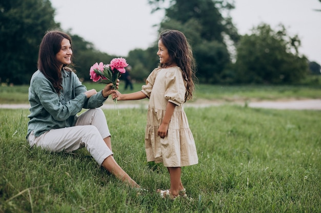 Klein meisje dat bloemen presenteert aan haar moeder
