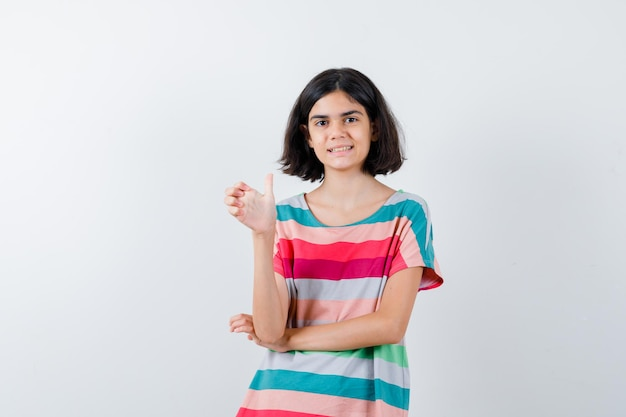Klein meisje dat de hand uitrekt als iets in een t-shirt, jeans en er gelukkig uitziet. vooraanzicht.