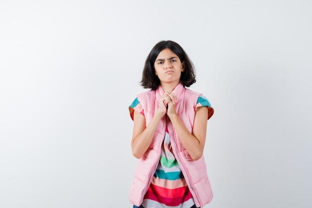 Klein meisje dat de handen in een t-shirt, puffervest, jeans klemt en er woedend uitziet. vooraanzicht.