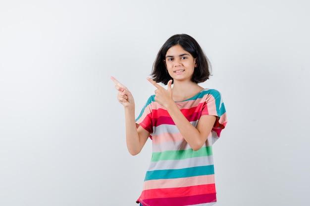 Klein meisje dat de linkerbovenhoek in een t-shirt wijst en er gelukkig uitziet. vooraanzicht.