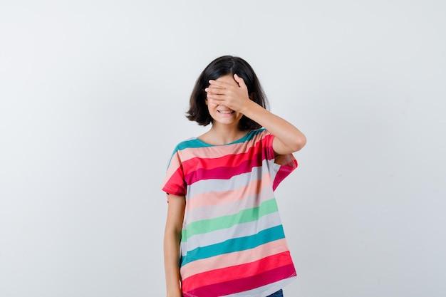 Klein meisje dat de ogen bedekt met de hand in een t-shirt en er gelukkig uitziet, vooraanzicht.
