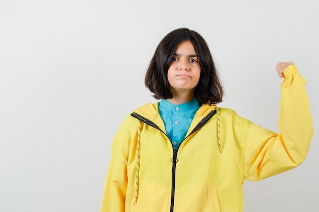 Klein meisje dat de spieren van de arm in shirt, jas toont en er zelfverzekerd uitziet. vooraanzicht.