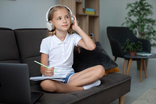 Klein meisje dat deelneemt aan online lessen terwijl ze een koptelefoon gebruikt