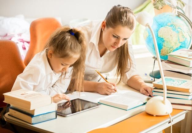 Klein meisje dat digitale tablet gebruikt terwijl moeder huiswerk maakt in plaats van haar