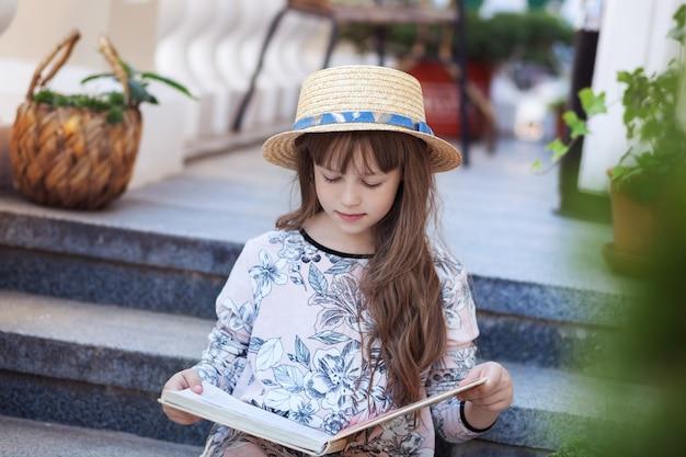 Klein meisje dat een boek leest over stappen van het huis kind leert lessen na school