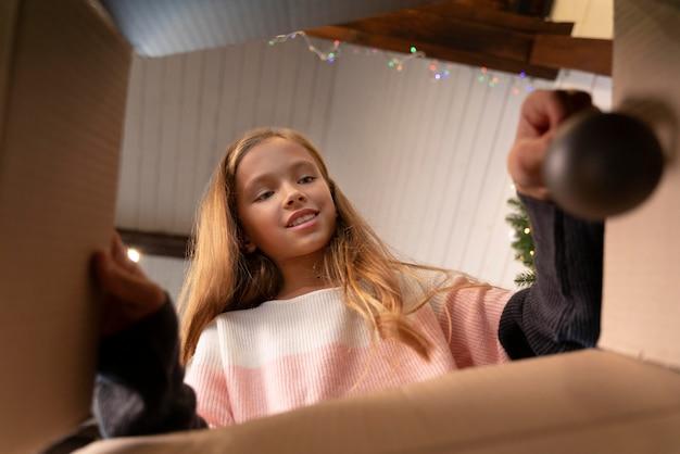 Klein meisje dat een boomversiering uit een doos haalt