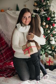 Klein meisje dat een cadeautje vasthoudt en haar moeder knuffelt voor de nieuwjaarsboom