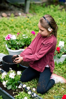 Klein meisje dat een dienblad met bloemen vult met aarde, bloemen verplant in de lente, voor planten zorgt.