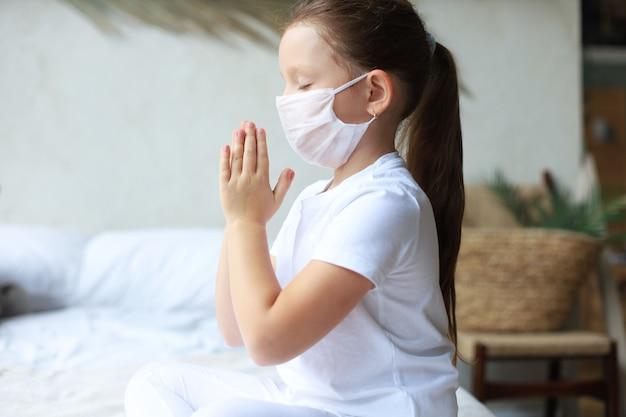 Klein meisje dat een masker draagt om covid-19 te beschermen. ze bad 's ochtends voor een nieuwe dag vrijheid voor het wereldwijde corona-virus. de hand van het meisje bidt voor god zij dank.
