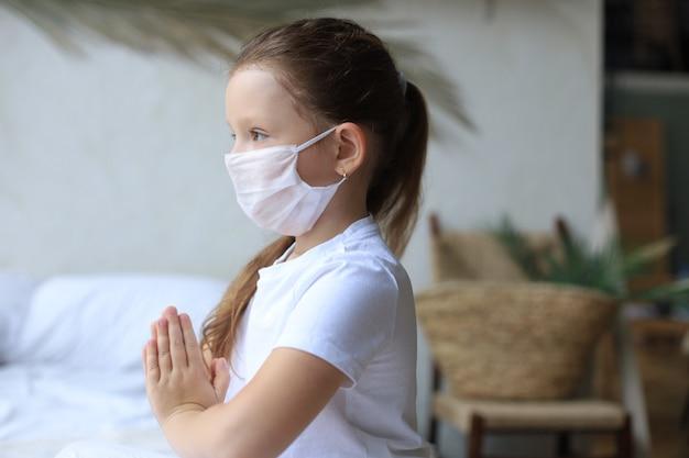 Klein meisje dat een masker draagt om covid-19 te beschermen. ze bad 's ochtends voor een nieuwe dag vrijheid voor het wereldwijde corona-virus. meisje hand bidden voor god zij dank.