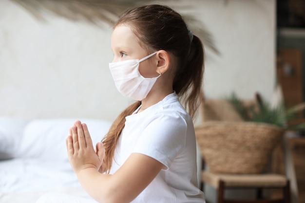 Klein meisje dat een masker draagt om covid-19 te beschermen. ze bidt 's ochtends voor een nieuwe dag vrijheid voor het wereldwijde corona-virus. meisje hand bidden voor god zij dank.