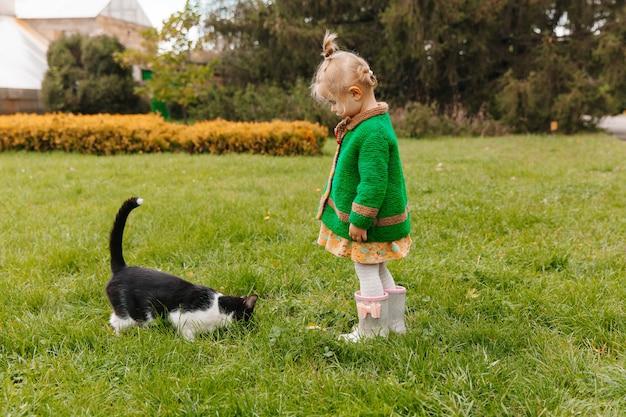 Klein meisje dat een zwarte kat in het park aait. meisje dat een kat aait. kinderen en dieren.
