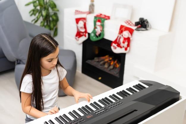 Klein meisje dat elektrische piano speelt met kerstmis
