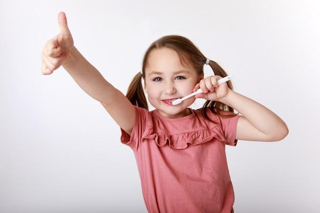 Klein meisje dat geniet van de dagelijkse routine van haar tanden poetsen