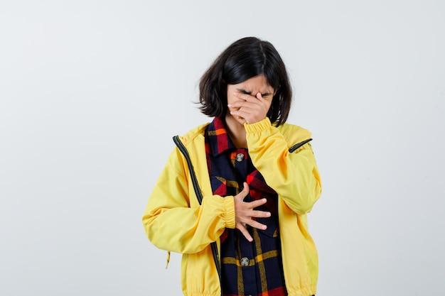 Klein meisje dat gezicht bedekt met hand in geruit overhemd, jasje en weemoedig kijkt, vooraanzicht.