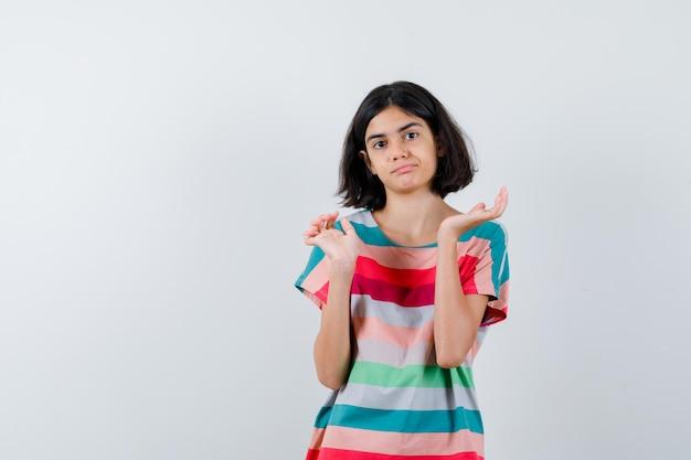 Klein meisje dat haar handen op een vragende manier in een t-shirt, spijkerbroek uitrekt en er verward uitziet. vooraanzicht.