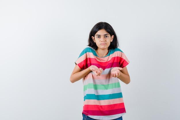 Klein meisje dat haar handen op een vragende manier in een t-shirt uitrekt en er verbijsterd uitziet. vooraanzicht.