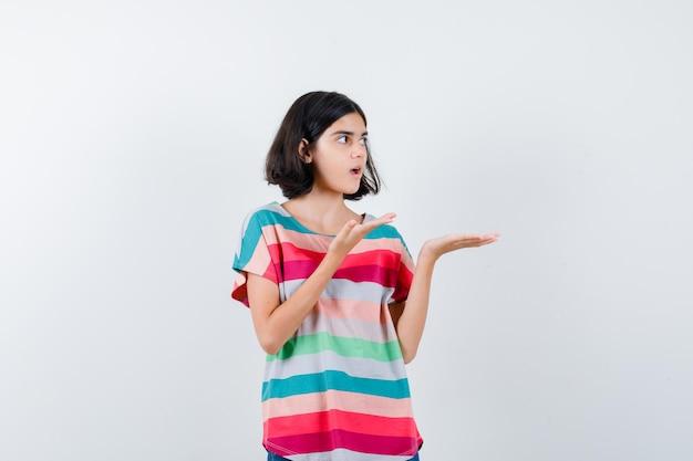 Klein meisje dat handen uitrekt als iets in een t-shirt, spijkerbroek en verrast, vooraanzicht.