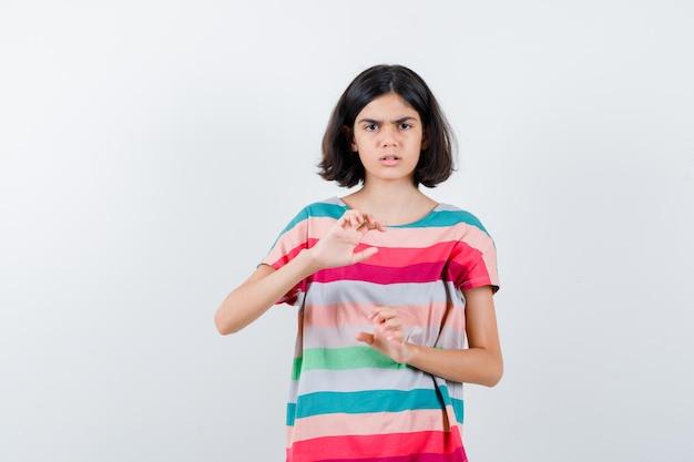 Klein meisje dat handen uitrekt alsof ze iets in een t-shirt vasthoudt en boos kijkt, vooraanzicht.