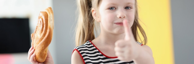 Klein meisje dat heerlijk zoet broodje eet en duim laat zien