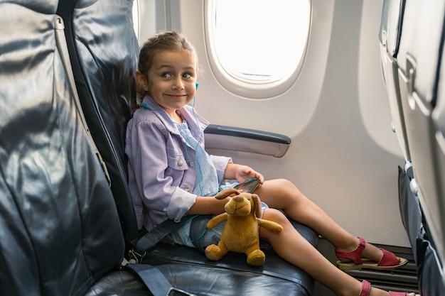 Klein meisje dat in een stoel in een vliegtuig zit en een telefoon vasthoudt