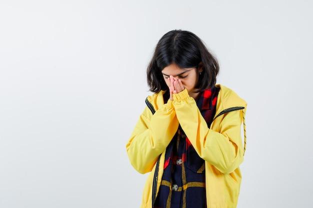 Klein meisje dat mond en neus bedekt met handen in geruit hemd, jasje en er attent uitziet. vooraanzicht.