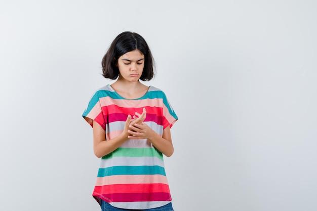Klein meisje dat naar de palm kijkt als iets in een t-shirt, spijkerbroek en gefocust. vooraanzicht.