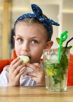 Klein meisje dat niet-alcoholische mojito drinkt en bitterkoekjes eet in een café