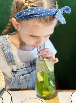 Klein meisje dat niet-alcoholische mojito drinkt in een café