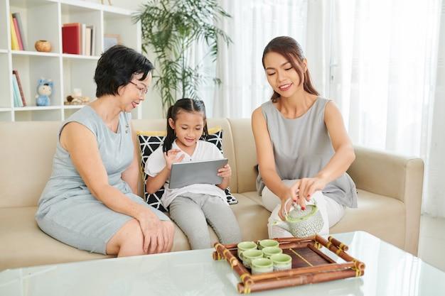 Klein meisje dat nieuwe applicatie of spel op tabletcomputer laat zien aan grootmoeder wanneer haar moeder groene thee in kopjes schenkt