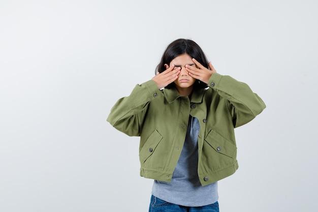 Klein meisje dat ogen bedekt met handen in jas, t-shirt, spijkerbroek en weemoedig kijkt. vooraanzicht.