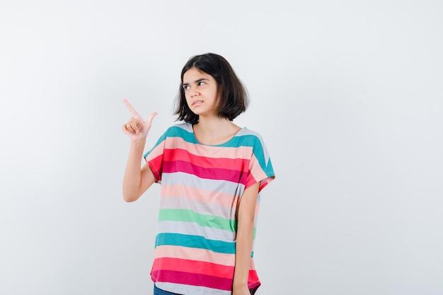 Klein meisje dat omhoog wijst, wegkijkt in t-shirt, spijkerbroek en er gelukkig uitziet, vooraanzicht.